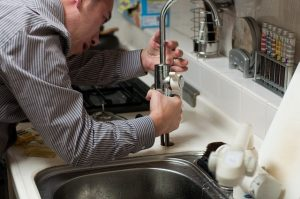 plumber fixing a leaking faucet